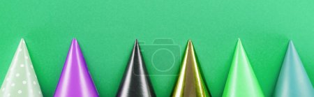 Photo for Panoramic shot of colorful party hats on green background - Royalty Free Image