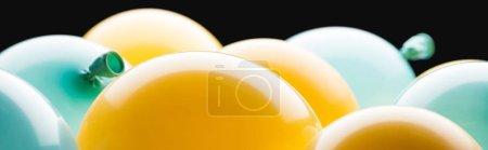 Photo pour Tir panoramique des ballons jaunes et bleus d'isolement sur le noir - image libre de droit