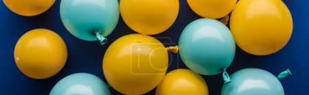 Panoramic shot of yellow and blue balloons decorative background