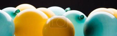Foto de Disparo panorámico de globos amarillos y azules aislados en negro - Imagen libre de derechos