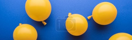 Photo pour Panoramic shot of festive yellow balloons on blue background - image libre de droit