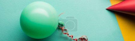 Foto de Foto panorámica de globo verde y sombrero de fiesta rojo sobre fondo tiffany - Imagen libre de derechos