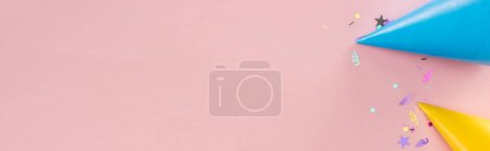Photo for Panoramic shot of blue and yellow party hats on pink background - Royalty Free Image