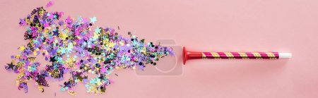 Photo for Panoramic shot of party horn with sparkling confetti on pink background - Royalty Free Image