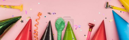 Panoramic shot of party decoration and party hats on pink background