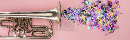 Photo for Panoramic shot of trumpet and colorful confetti on pink background - Royalty Free Image