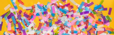 Photo for Panoramic shot of colorful confetti on yellow party background - Royalty Free Image