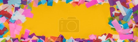 Foto de Panoramic shot of multicolored confetti frame on yellow background - Imagen libre de derechos