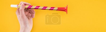 Panoramic shot of woman holding red party horn on yellow background