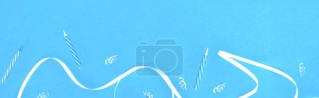Photo for Panoramic shot of white ribbon and candles on blue background - Royalty Free Image