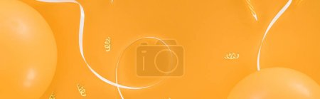 Photo pour Panoramic shot of yellow balloons and party decoration on orange background - image libre de droit