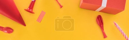 Photo pour Panoramic shot of red birthday party objects on yellow background - image libre de droit