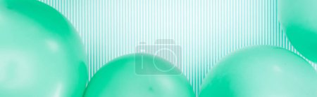 Photo for Panoramic shot of green balloons on blue and white striped background - Royalty Free Image