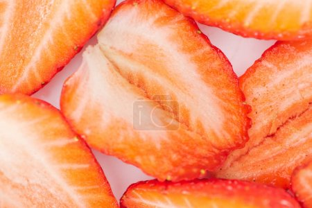 close up view of fresh cut ripe red strawberries in pile