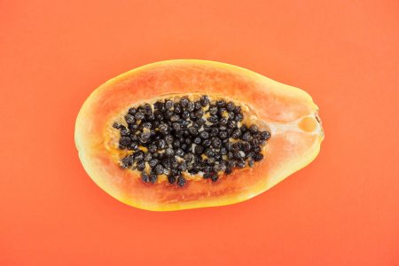 Photo for Top view of ripe exotic papaya half isolated on orange - Royalty Free Image