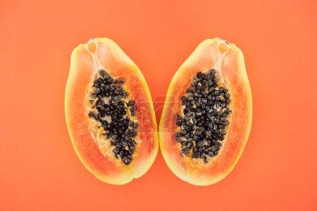Foto de Vista superior de las mitades de papaya brillante madura con semillas negras aisladas en naranja - Imagen libre de derechos