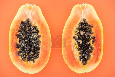 Photo for Top view of ripe exotic papaya halves with black seeds isolated on orange - Royalty Free Image