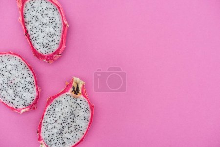 Photo for Top view of tropical ripe dragon fruit halves on pink background - Royalty Free Image