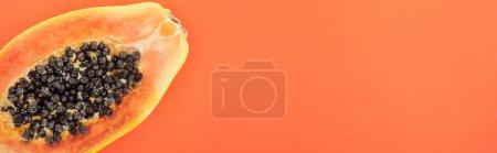 Foto de Foto panorámica de la mitad de la papaya exótica madura con semillas negras aisladas en naranja - Imagen libre de derechos