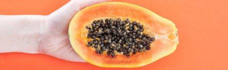 Foto de Foto panorámica de la mujer sosteniendo papaya exótica madura mitad con semillas negras aisladas en naranja - Imagen libre de derechos