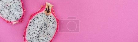 Foto de Foto panorámica de mitades de fruta de dragón maduro tropical sobre fondo rosa con espacio de copia - Imagen libre de derechos