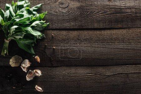 Photo pour Vue supérieure du basilic vert, des gousses d'ail et du poivre noir sur la table rustique en bois - image libre de droit