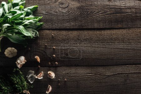 Photo for Top view of green basil, garlic cloves, thyme and black pepper on wooden rustic table - Royalty Free Image