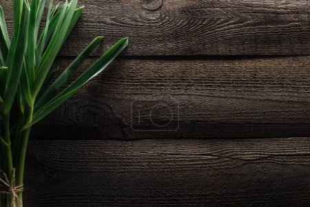 Photo for Top view of green leek on wooden rustic table - Royalty Free Image