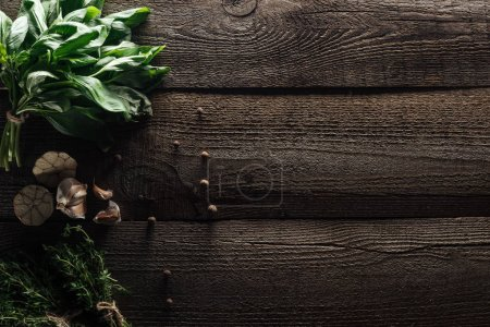 Photo for Top view of green thyme and basil near black pepper and garlic cloves on wooden weathered table - Royalty Free Image