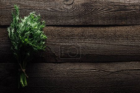 Photo for Top view of green dill on wooden weathered table with copy space - Royalty Free Image