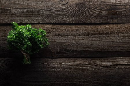 Photo for Top view of green parsley on wooden weathered table with copy space - Royalty Free Image
