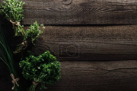 Photo for Top view of green onion, parsley, rosemary and thyme on wooden weathered table with copy space - Royalty Free Image