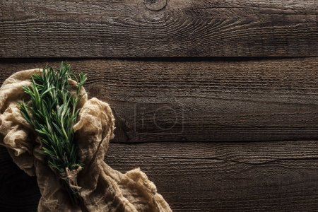Photo for Top view of green rosemary in rustic cloth on wooden weathered table with copy space - Royalty Free Image
