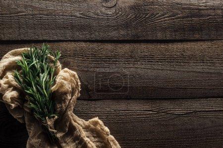 Foto de Vista superior de romero verde en tela rústica sobre mesa de madera desgastada con espacio de copia - Imagen libre de derechos