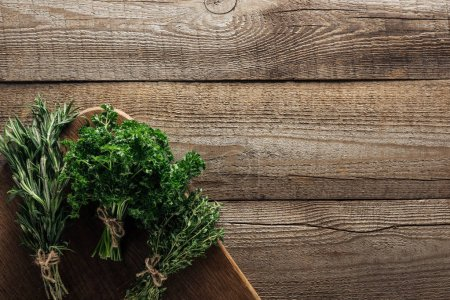 Photo for Top view of green rosemary, parsley and thyme on chopping board on wooden weathered table with copy space - Royalty Free Image