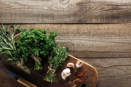 Photo for Top view of green thyme, parsley, rosemary on wooden chopping board near garlic cloves, knife, dried chili pepper and black pepper on wooden brown table - Royalty Free Image