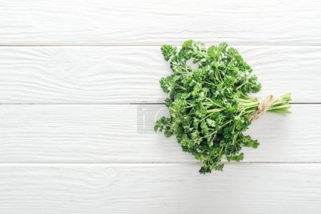 Photo for Top view of green parsley on white wooden table - Royalty Free Image