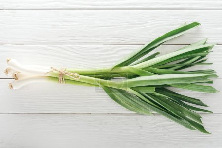 Photo for Top view of fresh green leek on white wooden table - Royalty Free Image