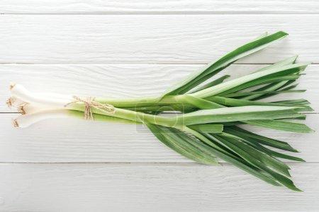 Photo pour Vue du dessus du poireau vert frais sur une table en bois blanc - image libre de droit