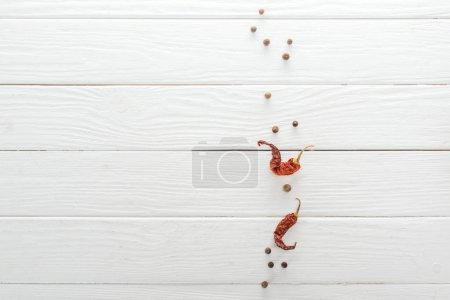 Foto de Vista superior de pimienta negra dispersa y chiles secos en la mesa de madera blanca - Imagen libre de derechos