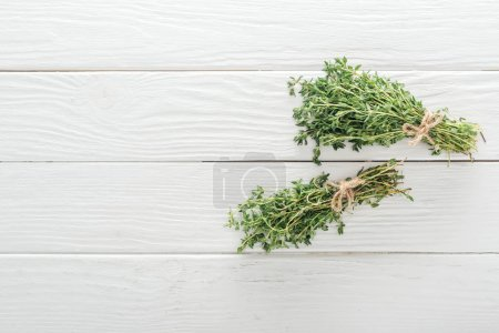 Photo for Top view of fresh green thyme on white wooden surface - Royalty Free Image