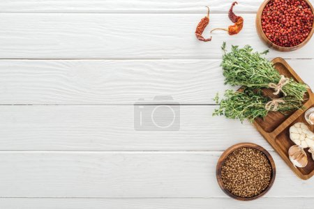 Photo for Top view of dried chili peppers, coriander and pink peppercorn in bowls near board with garlic cloves and thyme on white wooden table - Royalty Free Image