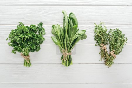 Photo for Top view of green parsley, basil and thyme on white wooden table - Royalty Free Image