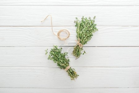 Photo for Top view of green thyme near thread on white wooden table - Royalty Free Image