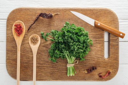 Photo for Top view of green parsley, knife, spoons with coriander and pink peppercorn, dried chili peppers on wooden chopping board - Royalty Free Image