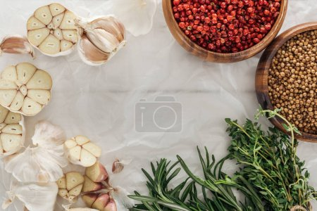 Photo for Top view of garlic cloves, pink peppercorn and coriander in bowls, rosemary and thyme on white paper background - Royalty Free Image