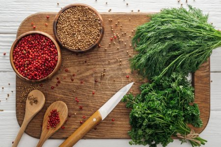 Photo for Top view of green parsley and dill, knife, spoons, coriander and pink peppercorn in bowls on wooden chopping board - Royalty Free Image