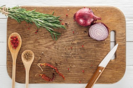 Photo for Top view of various spices and rosemary near knife on wooden chopping board - Royalty Free Image