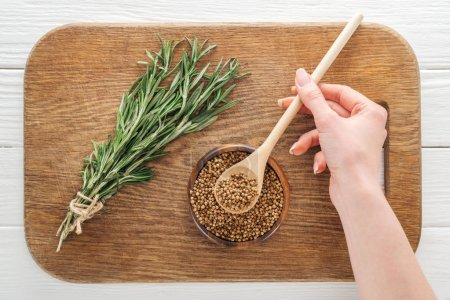 Photo for Cropped view of woman holding spoon with coriander near rosemary on wooden chopping board - Royalty Free Image
