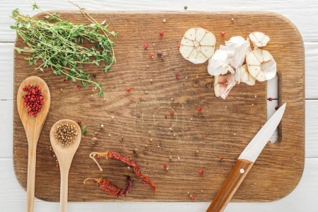 Photo for Top view of various spices and thyme on wooden chopping board - Royalty Free Image